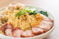 Egg noodle with red roast pork, crispy pork, dumplings and soup. Egg noodle with red roast pork, crispy pork, dumplings, soup and condiments royalty free stock images