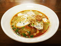 Egg noodle spicy soup with fish ball and shrimp ball. Egg noodle  tom yam soup with fish ball,  shrimp ball and green onion. This white bowl is served on wooden Royalty Free Stock Photography