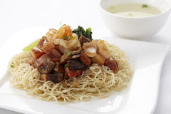 Egg noodle topped with stir fried ham and seafood Royalty Free Stock Image