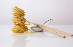 Egg noodles, ceramic spoon and wooden chopsticks Royalty Free Stock Photo