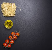 Egg noodles with cherry tomatoes and oil border ,place for text wooden rustic background top view Stock Image