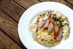Egg noodles with red roast pork, dumpling, wontons and veget Royalty Free Stock Images