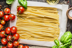 Egg Noodles in wrapping paper and fresh cooking ingredients: basil and tomatoes, top view Royalty Free Stock Image