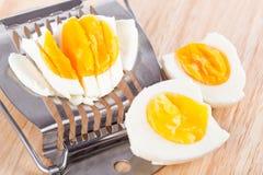 Egg o cortador e ovos cutted na tabela de madeira imagem de stock