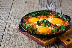 Egg o prato com o molho de tomate servido na bandeja do ferro fundido, shakshouka imagem de stock royalty free