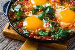 Egg o prato com o molho de tomate servido na bandeja do ferro fundido, shakshouka fotos de stock