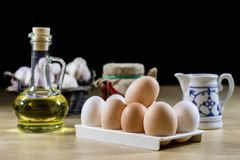 Egg, olive oil, spices on the kitchen table. Wooden table, kitch Stock Image