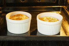 Egg omelet in white tins baked in the oven, breakfast for two portions, making food. Egg omelette baked in the oven in white tins, two servings of omelette for royalty free stock photos
