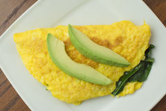 Egg omelete with spinach and avocado. High angle of egg omelete stuffed with spinach and topped with fresh sliced avocado on white plate stock images