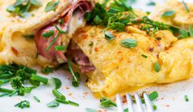 Egg omelette with ham and cheese sprinkled with chive. Egg omelette with ham and cheese sprinkled with green chive. Closeup stock images