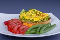 Egg omelette on a piece of fried bread with green beans, red tomato and carrot on a plate, close up. Breakfast concept Stock Photos