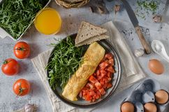 Egg omelette with salad. Perfect eggs omelette with vegetable salad, fresh arugula and juice royalty free stock photo