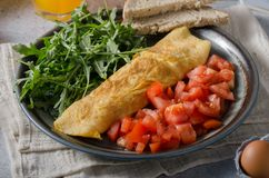 Egg omelette with salad. Perfect eggs omelette with vegetable salad, fresh arugula and juice royalty free stock image