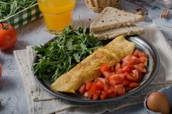 Egg omelette with salad. Perfect eggs omelette with vegetable salad, fresh arugula and juice royalty free stock photography