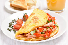 Egg omelette with vegetables and ham on white plate Stock Images