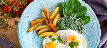 Egg over boiled spinach on blue plate. stock images