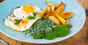 Egg over boiled spinach on blue plate. royalty free stock image