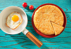 Egg over easy on white pan and potato omelette Royalty Free Stock Images