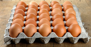 Egg in packet on wooden background Royalty Free Stock Images