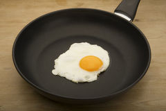 Egg in the pan. One single egg being fried in the middle of a small black frying pan royalty free stock image