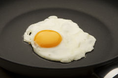 Egg in the pan. One single egg being fried in the middle of a small black frying pan stock images