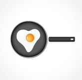 Egg in a pan in the form of heart Stock Image