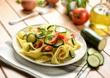 Egg pappardelle with zucchini and tomato - selective focus. Egg pappardelle with zucchini and tomato - closeup - selective focus Royalty Free Stock Photos