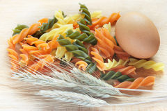 Egg, pasta and wheat. Egg, pasta and wheat on wood plate Royalty Free Stock Photography