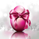 Egg with pink bow on silver bright background Royalty Free Stock Images