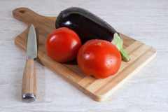 Egg-plant and 2 tomatos on a cutting board Stock Images