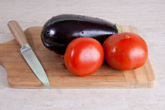 Egg-plant and 2 tomatos on a cutting board Royalty Free Stock Image