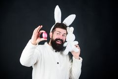 Egg play on Easter day. Bearded man in rabbit costume with easter egg and hare toy. Spring, new life and fertility. Spring holiday celebration. Happy man with royalty free stock photo