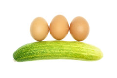 Egg put as straight and cucumber isolated Stock Photography