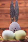 Egg-rabbit figure with big iron ears  near easter eggs Stock Photography