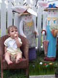 Is This Egg for Real?. Young boy sitting in a wicker chair with a white picket fence and two dressed easter rabbits beside him Stock Photo