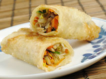 Egg Roll on a Plate. A delicious egg roll filled with chicken, napa cabbage, carrots, mung bean sprouts, wood ear fungus, and green onions Stock Image