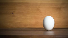 An egg is rolling across the table. Slow motion stock footage