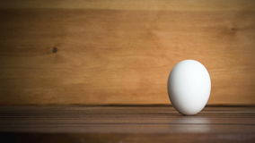 An egg is rolling across the table. Slow motion stock video footage