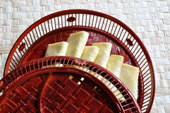 Egg rolls in bamboo basin with cover. Chinese egg rolls in a painted bamboo basin with cover Stock Images