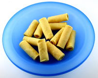 Egg rolls on blue plate. High angle view of egg rolls on blue plate with white background royalty free stock photos