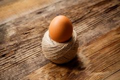 Egg in rope coil on old. Wooden table Royalty Free Stock Image
