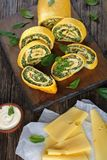 Egg roulade with spinach, carrots and cheese. Delicious egg roulade with a soft filling of mix of spinach, feta and carrots cut in slices  on wooden cutting Royalty Free Stock Image