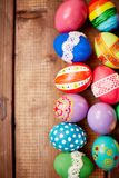 Egg rows. Two rows of painted eggs on wooden background Stock Photos