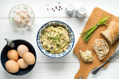 Egg salad in bowl topped with chives arranged on white table fro Royalty Free Stock Photography