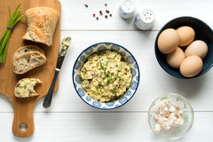 Egg salad in bowl topped with chives arranged on white table fro Royalty Free Stock Images