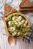 Egg salad in a wooden bowl and bread vertical top view Royalty Free Stock Photography