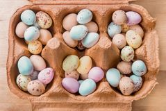 Egg Shaped Sweets Filling Carton Compartments. Overhead view of an opened brown egg carton, filled with piles of small egg shaped Easter sweets Stock Photography