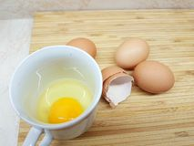 Egg shells. On a wooden cutting board, raw egg in a cup royalty free stock photo
