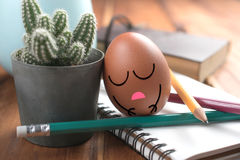 Egg with sleeping face on work desk relaxing and sleep from hard Stock Photos