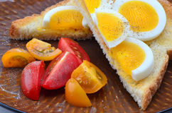 Egg slices on toast. Hard boiled egg slices on white toast and cherry tomatoes sprinkled with salt and pepper Stock Photos